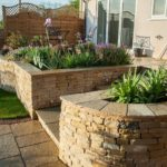 A raised bed built from cotswold dry stone walling with a surrounding limestone patio and a new planting scheme.