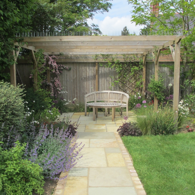Path leading to a seating area under a pergola.